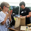 West Wind Cub Scout Day Camp, at the Paul Center in Chelmsford. Almost 200 campers attend the week-long program, with about 50 volunteer Boy Scouts and Girls Scouts helping out with the activities. Aidan Weinbeck 8, of Chelmsford, left, assembles a treasure chest, with help from volunteer Eli Henry, 12, of Tewksbury, in Woodworking. (SUN/Julia Malakie)