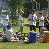 West Wind Cub Scout Day Camp, at the Paul Center in Chelmsford. Almost 200 campers attend the week-long program, with about 50 volunteer Boy Scouts and Girls Scouts helping out with the activities. Scouts cook sausages in crescent rolls over a fire in the Cooking activity. (SUN/Julia Malakie)