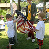 West Wind Cub Scout Day Camp, at the Paul Center in Chelmsford. P.J. McMahon, left, and Andrew Almeda, both 7 and from Wilmington, learn the proper way to raise and lower the flag in Scoutcraft, from David Rzeszut, 16, of Billerica, rear, also a Boy Scout. (SUN/Julia Malakie)