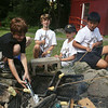 West Wind Cub Scout Day Camp, at the Paul Center in Chelmsford. From left, volunteer Shane Fannon, 11, of Westford, and campers Aiden Moynihan, 9, Owen Schultz, 9, and Matthew Fan, 9, all of Westford, cook sausages in crescent rolls at the Cooking activity. (SUN/Julia Malakie)