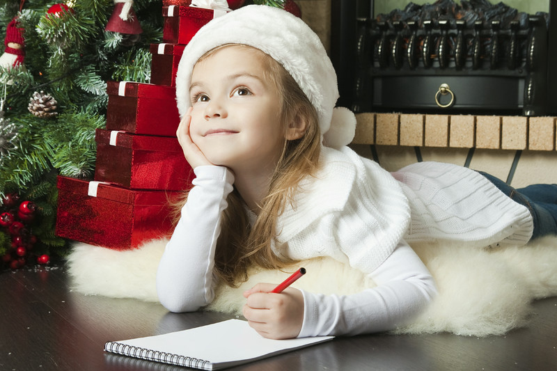 Pretty girl in Santa hat writes letter to Santa