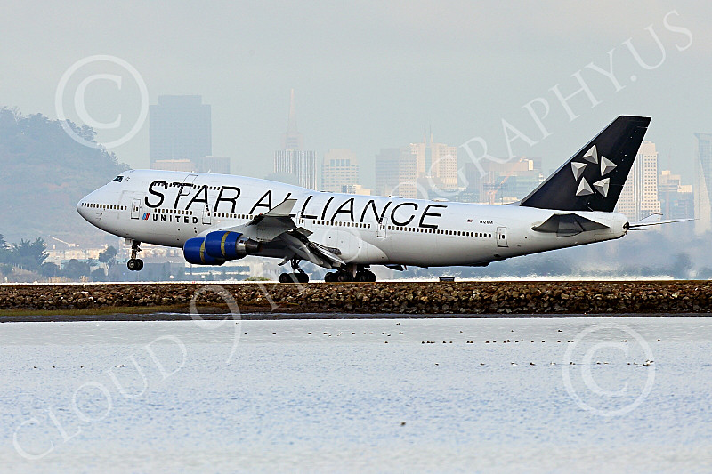 B747 01521 A Boeing 747 United Airline STAR ALLIANCE N121UA rolls out after landing at SFO with San Francisco's sky line in the background 12-2014 airliner picture by Peter J Mancus