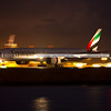 Emirates Boeing 777-300/ER lands at Sydney airport in darkness, with the lights of Port Botany shipping terminal in the background.