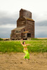 Woman in a green dress near a grain elevator
