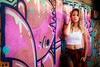 Beautiful woman in front of a graffiti covered wall