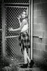 Beautiful young woman against a chain link fence