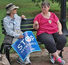 "Two women sitting on bench, one gesturing with hand, one holding ""stop keystone"" pipeline sign."