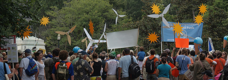 Large crowd of people at climate change rally, seen from behind, banners and windmills above them.