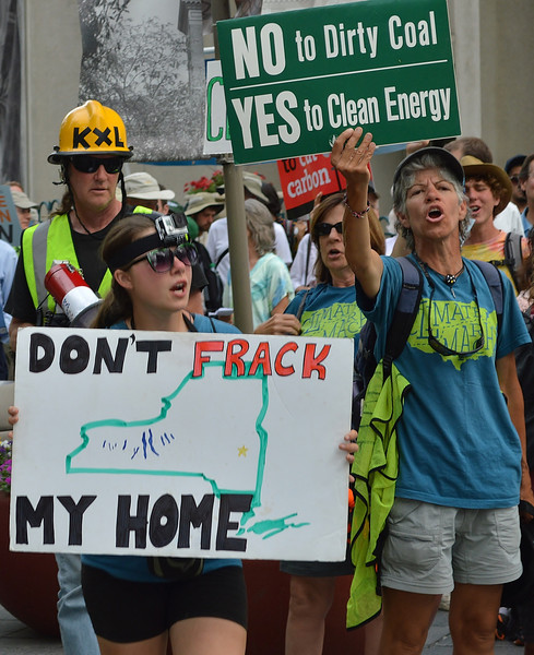 Two women raise signs at climate change protest, one with sign about coal and clean energy, the other  with sign about fracking with map of New York state on it.