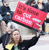 "Woman holding up ""cut carbon"" sign."