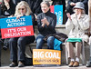 Three women sitting on step, one holding sign about climate change, two applauding.
