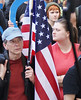 Young woman in profile standing next to man holding American flag, another young woman behind them.