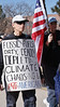 Man with sign about fossil fuels next to man with American flag, at climate change protest.