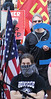 Young woman with bandana covering face, American flag besde her, at global warming protest.