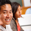 asian man in classroom with other students smiling at the camera