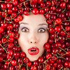 Woman's face emerging from a vat of cherries