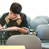 Last student taking a test in an empty lecture hall and classroom