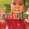 "Little boy holding wooden blocks spelling ""learn"""