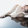 Glamorous young woman leaning over with bare arms on luminous mirrored surface