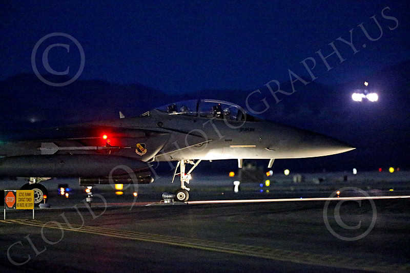 F-15EUSAF 01051 A USAF McDonnell Douglas F-15E Strike Eagle crew waits to take off as a USAF B-1 Lancer jet bomber takes off in full afterburner for a night Red Flag mission at Nellis AFB 7-2014 military airplane picture by Peter J Mancus