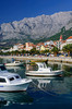 The harbor with a waterfront walk and fishing boats in Makarska, Croatia.