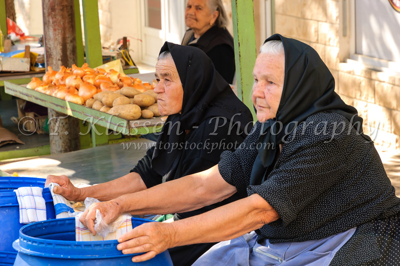 Ladies in ethnic dress selling fresh produce for sale at the city market in Split, Dalmatia, Croatia.