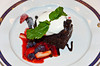 A chocolate fudge cake with fresh fruit and glaze served as a dessert on the Holland America cruise ship Zuiderdam.
