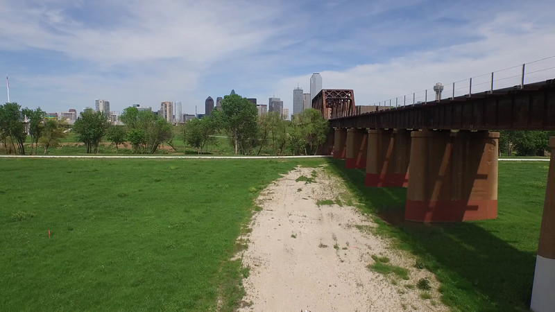 DALLAS SKYLINE FROM THE TRINITY RIVER TRUCKING SHOT UP