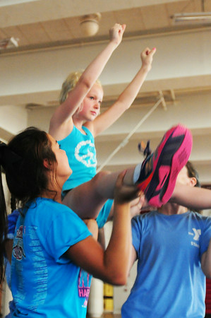 BRYAN EATON/ Staff Photo. Abby Joyner, 8, of Newbury does some cheering acrobatics at Newburyport High School, part of the Newburyport Youth Services Summer program. High school cheerleading coach Nadine Holohan lead the camp with help from her cheerleaders.