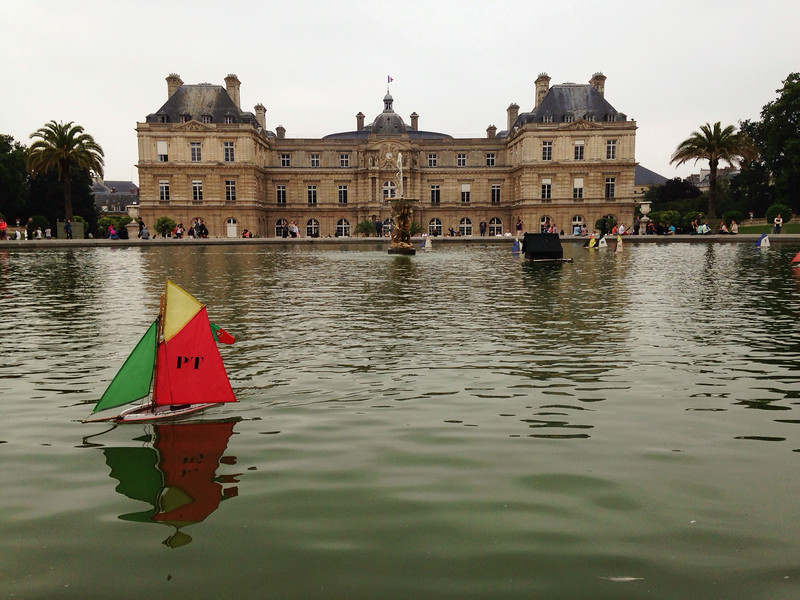 2014-07-22<br /> Portugal Ship<br /> At Luxembourg Gardens, kids rent little sailboats of countries or animals and push them across the giant fountain. The palace buildings are now used by the Senate. <br /> We spent some nice relaxing time at the gardens after walking through the Latin Quarter of Paris. We also did other stuff, but I'll share those photos later.