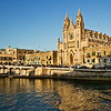 Our Lady of Mount Carmel Church is bathed in golden light from the setting sun on Baluta Bay in St. Julian's, Malta.