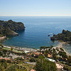 Taromina, Sicily, sits high atop rock cliffs, overlooking the beaches of Isola Bella Bay and pretty little Isola Bella Island. Access to the city center from the beaches is via steep stairs or a nearby cable car.