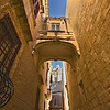 Stone bridge between buildings frames St. Paul's Cathedral in the old walled city of Mdina on the island of Malta.