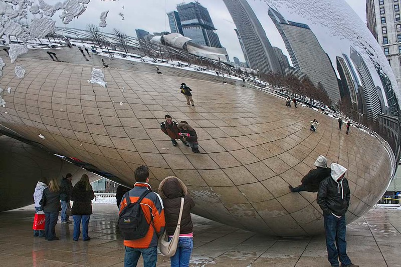 """Visitors to Chicago are fascinated by the highly polished surface of """"The Bean"""" sculpture in Millennium Park"""