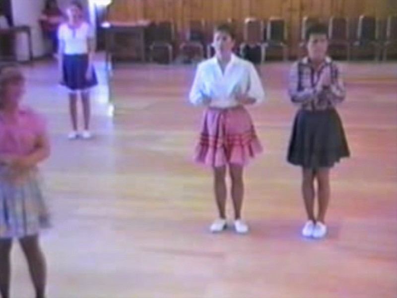 """Video Archive Clip 1987 (Aug) - Yaden Clogging - Julie Yaden (age 33, center in white blouse/pink skirt) dancing the """"I'm Your Man"""" routine with her 'sister from another mister' Sher Francis (far right in black skirt) - Instructor: Linda Casaw - Moxee Grange Hall - Moxee, WA<br /> <br /> Dan's note:<br /> <br /> During most of 1987 (we moved to Texas in December) Julie and I had a lot of fun attending dances and workshops with clogging friends from both Yakima and Seattle groups.  In the summer of '87 Julie became great friends with Sher Francis, a clogger and instructor from Tacoma.  We all thought the two had to have been sisters in a previous life......<br /> <br /> (In case you're wondering, the man who enters the frame late in the routine toward the back wearing a yellow shirt and performing organized stumbling is me.......I have no further comment.)"""