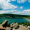 Hiker's view of blue skies and trees and and quartzite boulders framing turquoise Devils Lake along East Bluff Trail within Devils Lake State Park (USA WI Baraboo)