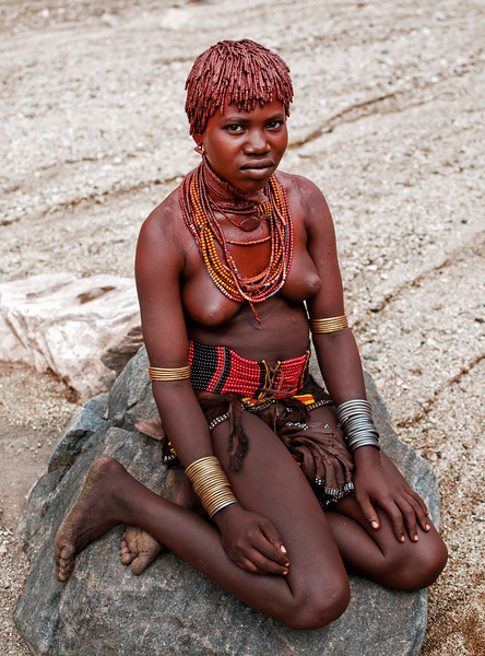 This is Galtier, a young Hamar woman. Galtier is the first and for now at least the only wife as symbolised by her necklace. First wives have a privileged position since the others that come later get to do most of the heavy work including giving birth.   Omo Valley, Southern Ethiopia, 2013.