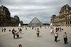 Leaving the Louvre courtyard and approaching more of the complex including the glass pyramid.