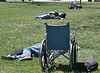 Homeless man sleeping on the ground in a park, wheelchair next to him, in the background, other people sleeping on the ground.