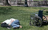 Homeless man sleeping on the ground in a park, wheelchair next to him.