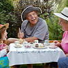 Grandparents and beautiful grandaughter having fun at a tea party