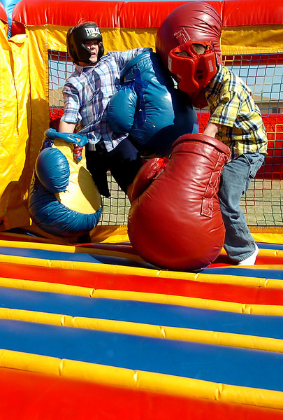 Christian Skalla (left) and Logan Green exchange punches in the inflatable boxing ring during Oakwood Christian Church's Easter Eggstravaganza Saturday, April 19, 2014. (Staff Photo by BONNIE VCULEK)