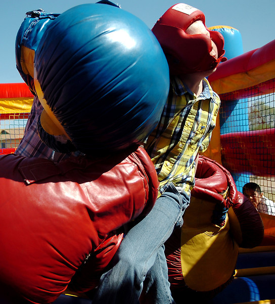 Christian Skalla (left) lands a punch on Logan Green in the inflatable boxing ring during Oakwood Christian Church's Easter Eggstravaganza Saturday, April 19, 2014. Six egg hunts, inflatables, food and games were prepared for the community event. (Staff Photo by BONNIE VCULEK)
