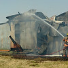 Enid firefighters battle a fire at 3011 W. Phillips Road Thursday, August 21, 2014. A rural postal carrier noticed the flames at 10:37 a.m. and called 911. The structure, on the property of active Enid firefighter Tim Dowers, was a total loss. The Enid Fire Department, Enid Police Department, and Kremlin-Hillsdale Volunteer Fire Department responded to the scene. (Staff Photo by BONNIE VCULEK)