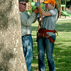 Jim Mitchell (left), from Professional Tree Care, explains the art of tree climbing to Grace Dewald after Dewald's husband, Drew, arranged for the special 21st birthday tree climbing lesson at Government Springs Park Saturday, July 26, 2014. (Staff Photo by BONNIE VCULEK)