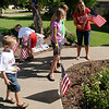 Larissa Bragg (right) and her four children decorate their lawn with American flags and other patriotic designs before leaving for Will Rogers Airport in Oklahoma City to welcome home Capt. Joel Bragg. Capt. Bragg, who is stationed at Vance Air Force Base, just completed a one-year tour of duty in Afghanistan and will return to Enid later today. (Staff Photo by BONNIE VCULEK)