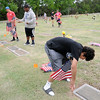Enid High School Plainsmen football players place United States flags on the graves of veterans at Memorial Park Cemetery as they honor their memory for Memorial Day weekend Friday, May 23, 2014. (Staff Photo by BONNIE VCULEK)