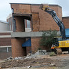 An employee with American Demolition and Site Services, LLC uses an excavator to remove the brick from the Cherokee Strip Conference Center Friday, Nov. 22, 2013. Demolition of the conference center and the Kress Building will make way for the new downtown Enid hotel. (Staff Photo by BONNIE VCULEK)