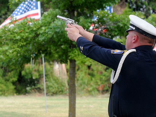 "A member of the Enid Police Department Honor Guard fires his weapon during a 21-gun salute to fellow officer, Sgt. Richard Allan ""Rick"" Tanner, II, during a rememberance ceremony at Memorial Park Cemetery. (Staff Photo by BONNIE VCULEK)"