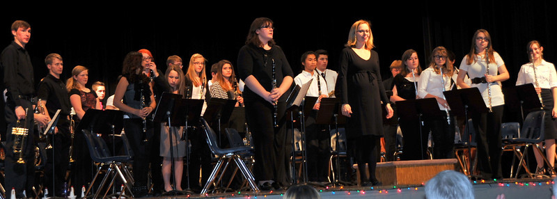 The Sterling High School concert band and director Sarah Vogel stand for applause at the end of the SHS Bands Winter Concert, Monday, Dec. 16, 2013.